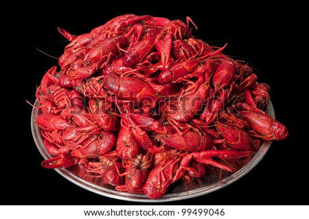 A plate with many red cooked crayfish stacked in a pile. Isolated on black