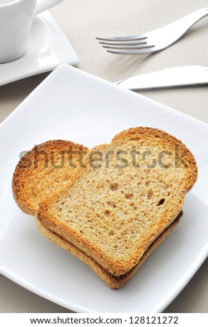 a plate with two bread rusks forming a heart on a table with a cup of coffee