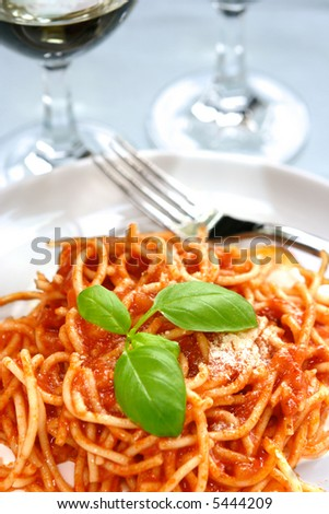 A plateful of delicious spaghetti in tomato sauce with parmesan cheese sprinkle.