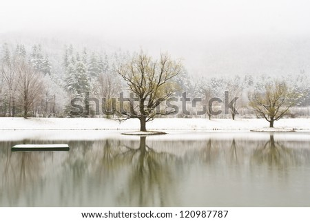 A platform and islands on a calm Catskills lake with snow-covered mountains behind near Big Indian, New York