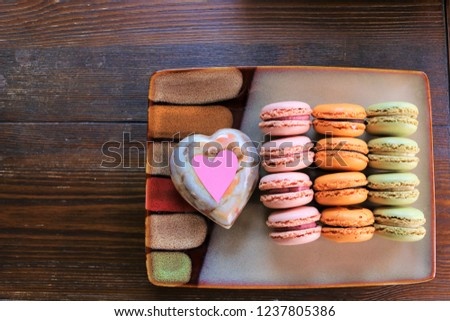 A platter of colorful french macrons, with a stone heart and a pink heart, placed on a wooden brown table. Concept of love, mother's day, Valentine's day, food, women's day, celebration, cafe etc. #1237805386