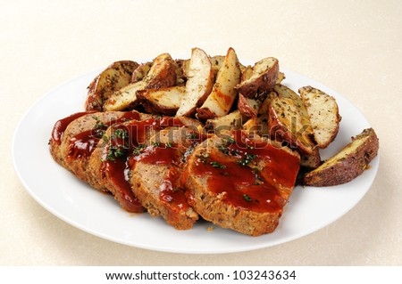 A platter of sliced meatloaf with sliced potatoes