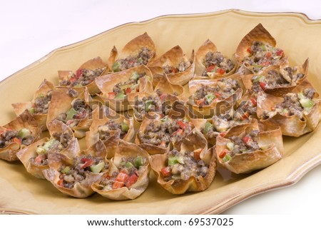 A platter of won ton wrapped appetizers on a gold platter