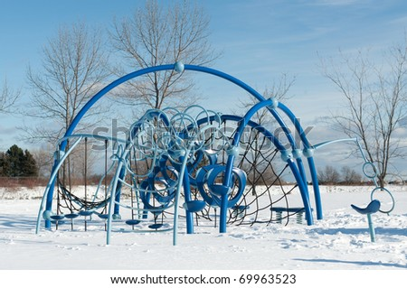 A play structure at a childrens' playground in winter.