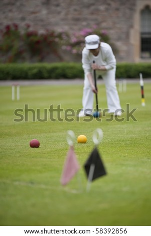 A player concentrating on a strike during game of croquet