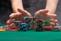 A player playing in a casino raises the bet with chips effectively with smoke. Gaming business