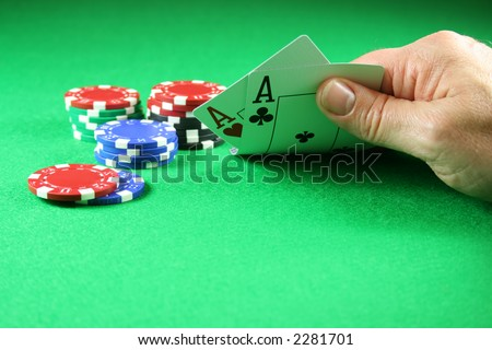 A player showing a pair of aces with poker chips next to them - stock photo