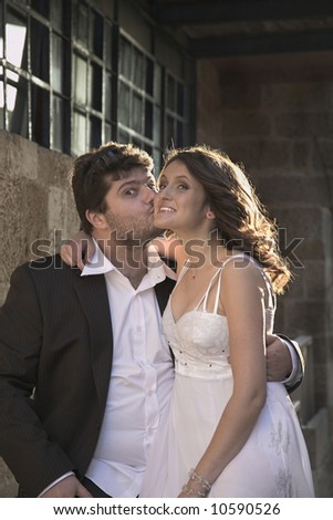 A playful kiss for show in execution of the young and beautiful groom and the bride.
