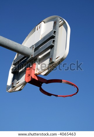 A playground basketball hoop against a blue sky.