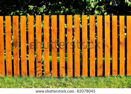 A pleasant sunny backyard with green grass and a nice wood fence. - stock photo