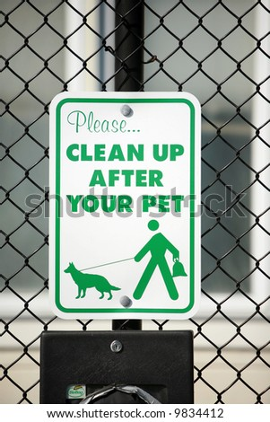 "a ""please clean up after your pet"" sign in a park"