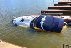 A pleasure boat sinks in murky water.