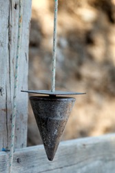 A plumb bob, or plummet, a weight, usually with a pointed tip on the bottom, suspended from a string and used as a vertical reference line, or plumb-line.