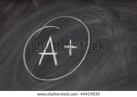 A plus grade handwritten with white chalk on blackboard with eraser smudge texture