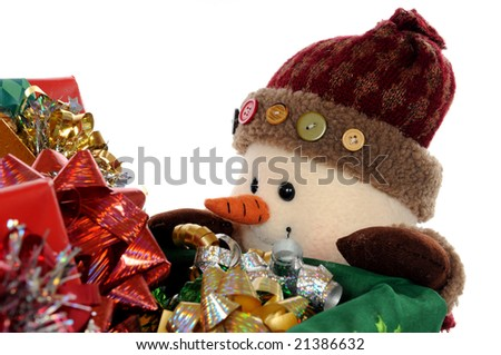 A plush snowman peeking over the top of a cart full of wrapped Christmas gifts.  Isolated on white.