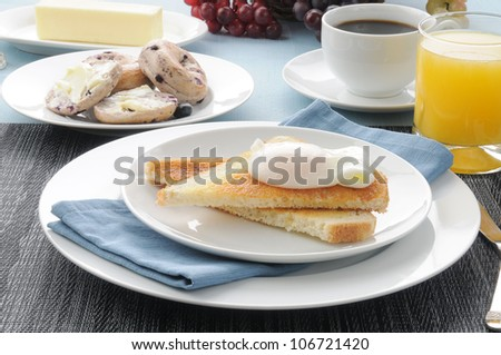 A poached egg breakfast with blueberry bagels