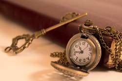 A pocket watch and a key resting against an old book. a concept of time and freedom.