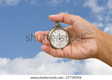 A pocket watch in hand on a sky background, pocket watch