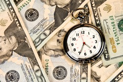 A pocket watch, or clock, timepiece on a pile of cash.  Good use for any financial inference where time is a factor of money, investment and growth.