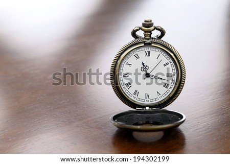 A pocket watch showing the time as seventeen minutes after eleven.