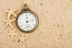 A pocket watch with starfish in the sand on the beach, summer vacation