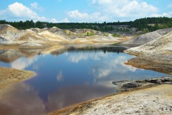 A poisonous, acidic lake in the middle of colorful, lifeless clay hills and a blue sky with clouds. Open pit mining. A green forest in the background. Blue sky and clouds are reflected in red water.