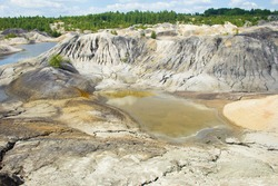 A poisonous, acidic lake in the middle of colorful, lifeless clay hills and a blue sky with clouds. Open pit mining. The industrial landscape is similar to the Martian landscape.