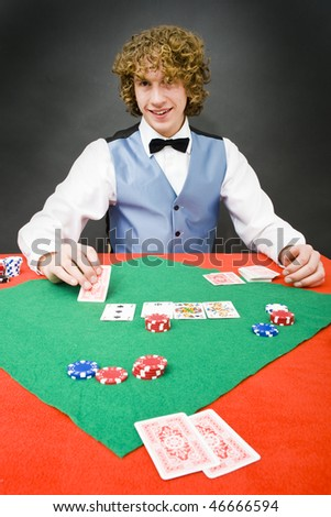 A poker dealer smiling friendly at a player during a casino game