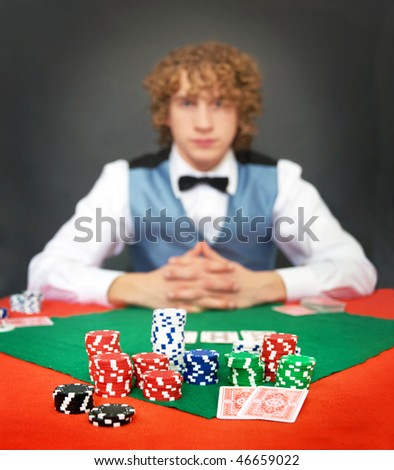 A poker player facing the dealer over a stack of chips. Shallow DOF, focus on the front row of chips
