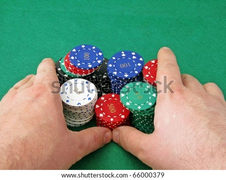 A poker players hands pushing in all his chips on a green felt background