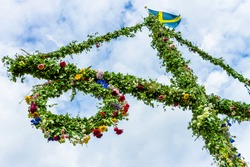 A pole and flag against blue sky and white clouds. A maypole decorated, covered in flowers and leaves.
