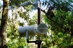 A pole with a camera and loudspeakers surrounded with green trees in the park