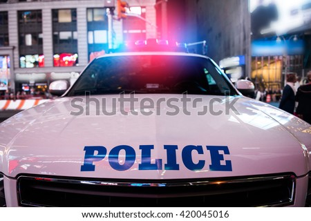 A police car rushes to the emergency call with lights turned on in the city street