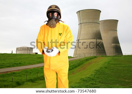 a police man or security guard in a yellow rain suit or anti Radiation Suit is worried about the readings he is getting on his Geiger counter while infront of  Nuclear Generator Cooling Towers