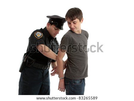 A police officer arrests and handcuffs a young male teen felon.