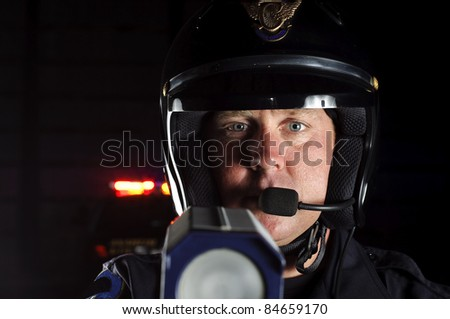 a police officer at night pointing his radar gun at traffic.
