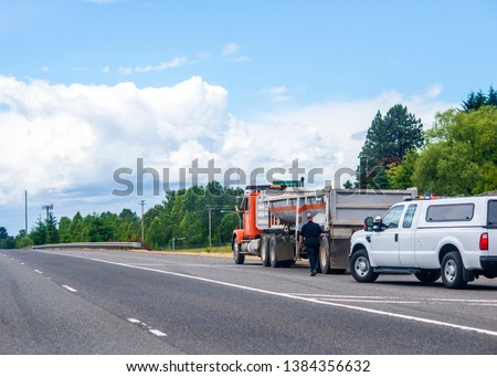 A police officer in uniform stopped a big rig semi-truck for check a truck driver and inspection of a tip truck and approaches to the truck on the side of the road, visually inspecting a tip truck