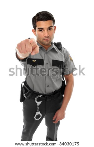 A police officer, prison guard or similar uniformed man stands firm with pointed finger.  Concept