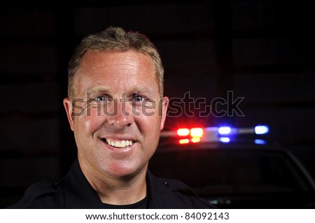 A police officer smiling in the night with his police car in the background.