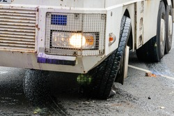 A police water cannon suffers damage to its tyre during a riot