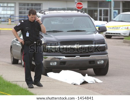 A policeman makes a cell call while standing beside a shooting victim.