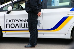 A policeman stands near a patrol police car with the inscription in Ukrainian Patrol Police, Dnepropetrovsk, Dnipro city. Ukraine police, policeman Ukraine