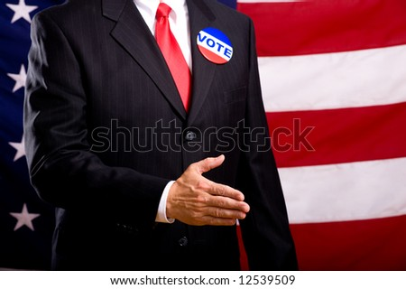 A politician in a blue suit and red necktie extending his hand to be shaken.  Standing in front of an American flag.  shallow depth of fiield focus is on hand and then falls off