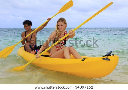 A Polynesian man and a blond caucasian girl, wearing leis, paddle their ocean kayak towards shore
