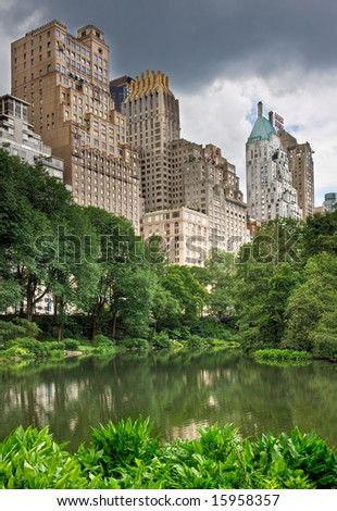 A pond in central park with high rise buildings behind it in New York City #15958357