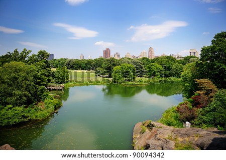 A pond in New York City Central Park in summer with a view of Manhattan skyscrapers and colorful trees