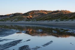 A pond in the middle of sandy coast in the evening in Norderney