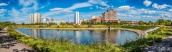 A pond on Privolnaya Street with a view of high-rise residential buildings and a school on a sunny autumn day. Zhulebino district, Moscow. Panorama.