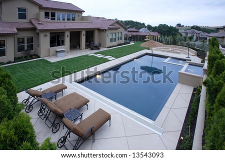 A Pool With A Waterfall In A Luxury Backyard With New Landscaping ...
