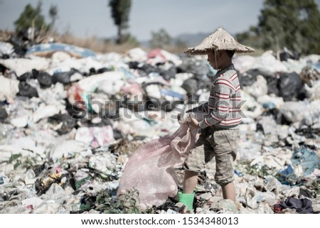 A poor boy collecting garbage waste from a landfill site in the outskirts .  children work at these sites to earn their livelihood. Poverty concept.